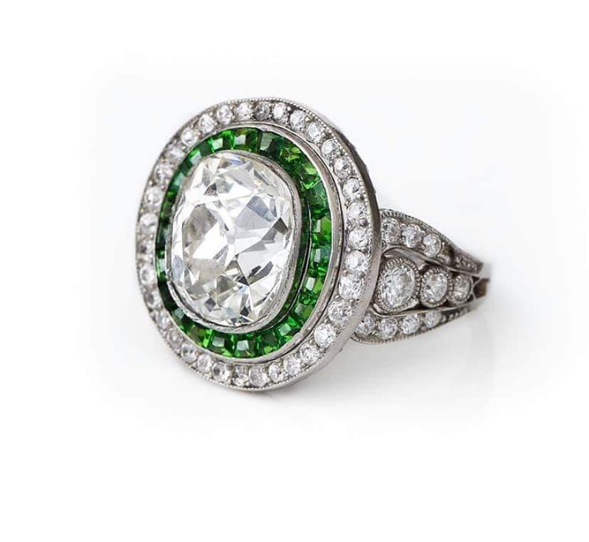 Elegant white gold and diamond ring with emerald accents